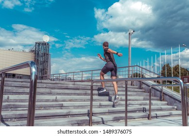 Male athlete jumping in the morning on a run, sportswear, summer fitness in the city, free space for text. Active lifestyle. Steps and blue clouds background
