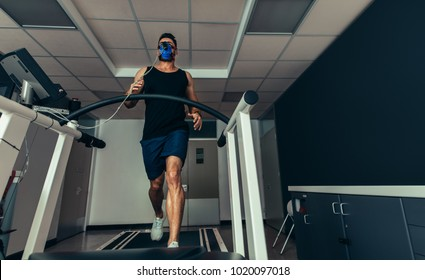 Male athlete with mask running on treadmill to analyze his fitness performance. Runner testing his performance in sports science lab.