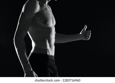 male athlete with naked body shows thumb up on a dark isolated background