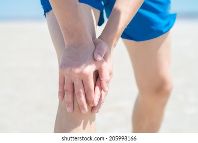 Male athlete on floor clutching knee and hamstring in excruciating pain on white background