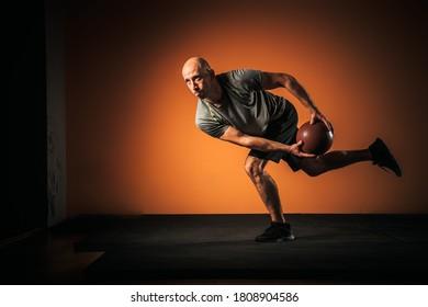 Male athlete performing functional training with medicine ball.