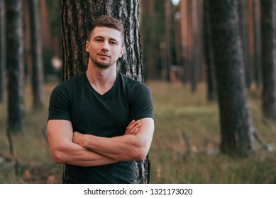 Male athlete posing in the woods on a background of a tree behind his back. Active lifestyle fitness, workout on the street. Powerful confident and strong pumped guy. Free space for text.