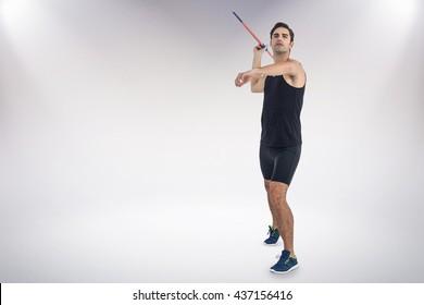 Male athlete preparing to throw javelin against grey background