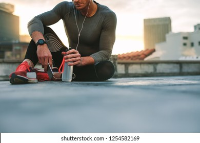 Male athlete relaxing after workout listening to music on earphones using mobile phone. Fitness man taking a break from workout sitting on rooftop holding cell phone and water bottle.