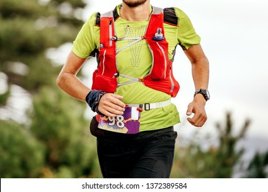 male athlete run mountain race with hydratation trail vest for running