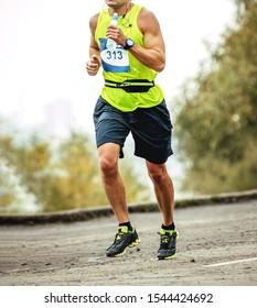 male athlete runner with bottle of water in hand running marathon