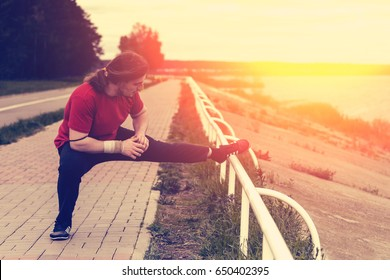 Male athlete runner doing hard legs exercise stretching, preparing for workout in the park at sunset