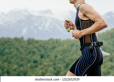 male athlete runner with energy gel in hand running on mountain marathon