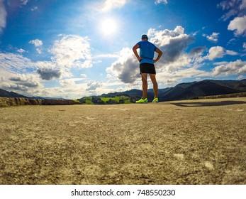 Male athlete runner resting at blue sky background