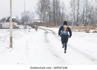 Male athlete runner, running on the road in winter