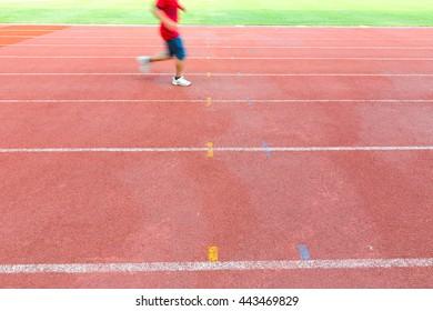 Male athlete running on the red running track in athletics stadium.