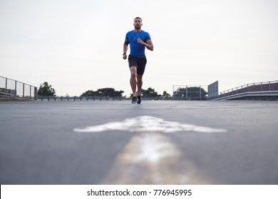 Male athlete running on a road towards camera, full length