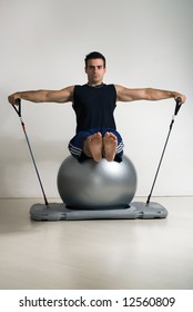 Male athlete sitting, arms extended, doing Pilates.