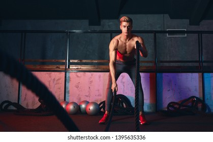 Male athlete stops doing boring cardio workouts and starts using the battle ropes to really crank it up. Man will easy get winded, fatigued and burn those calories faster with these moves