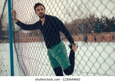 Male athlete stretching quadriceps on the fence on a snowy day