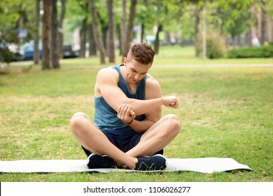 Male athlete suffering from elbow pain during training outdoors