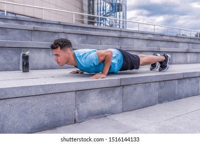 male athlete, tanned man, summer city, push-ups, lying on bench, chest training, bar on press, bottle of protein with water, fitness workout, background concrete steps. Free space for motivation text