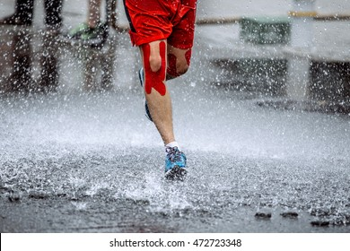 male athlete with tape on his knees running through a puddle of water, splashes and drops around feet