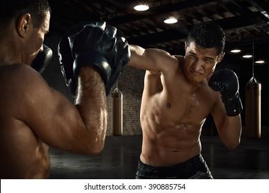 Male athlete training boxing skills at gym