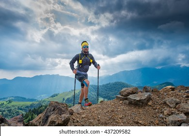 Male athlete true top halls of a mountain with sticks behind panorama of mountains