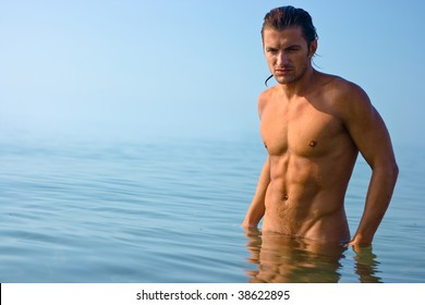 Male athlete with very muscular figure standing in sea water