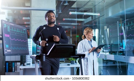 Male Athlete Walks on a Treadmill with Electrodes Attached to His Body while Sport Scientist Interacts with Touchscreen and Supervises EKG Status. In the Background Laboratory with High-Tech Equipment