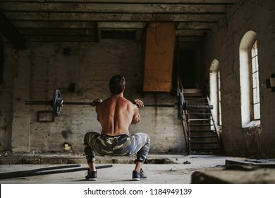 Male athlete workout legs by doing front squat in old abandoned building