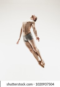 The male athletic ballet dancer performing dance isolated on white background. Studio shot. Ballet concept. Fit young man. Caucasian model