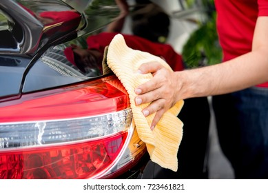 Male auto care service staff cleaning car tail light with microfiber cloth