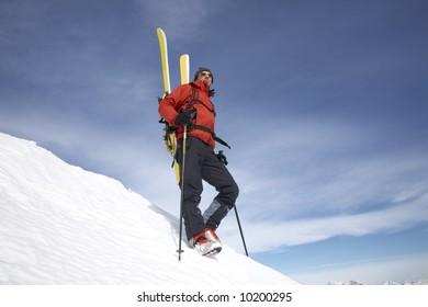 Male backcountry skier against blue sky; italian alps