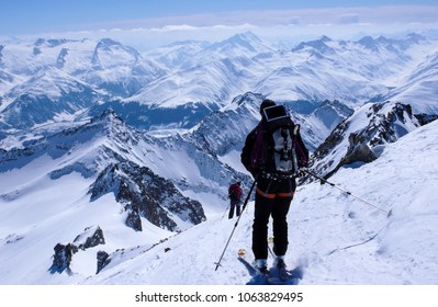 male backcountry skier skiing down from a high alpine summit with a large backpack and solar panel