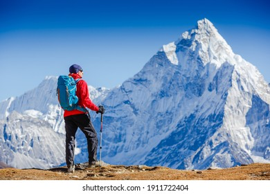 Male backpacker enjoying the view on mountain walk in Himalayas. Ama Dablam mountain view.Travel, adventure, sport concept