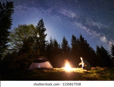 Male backpacker sitting alone near tourist tent at burning campfire on grassy valley, enjoying night blue starry sky, Milky way, pine trees forest on background. Tourism and mountain camping concept