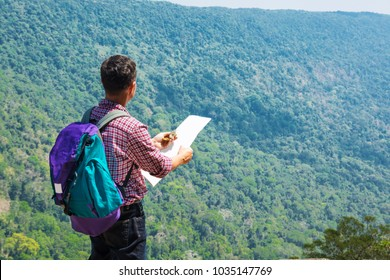 Male Backpacker Traveler or Trekker Stand on Cliff use Navigation map and Compass while Hiking on Green Nature Mountain as Traveling Equipment Concept