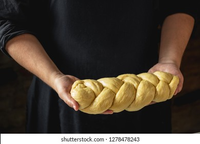 Male baker holding loaf of raw challah jewish bread
