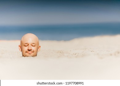 Male bald head above sand.  Man buried  alive in desert. Punished boy suffering in uninhabited beach on sun. Closeup portrait of funny guy taking sunbath with body under ground near ocean. Therapy