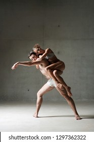 Male ballet dancer carrying lifting female dancer on back, romantic performance, trust support control coordination on stage, indoors. Concept harmony power control, strong teamwork.