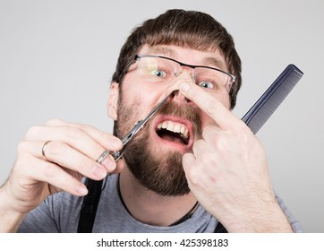 male barber cuts his own hair in the nose, looking at the camera like the mirror. stylish professional hairdresser expresses different emotions