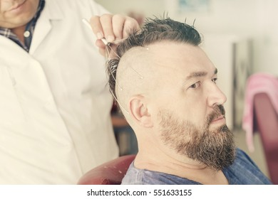 Male barber doing massage using capillary head massager of a adult bearded man with a mohawk