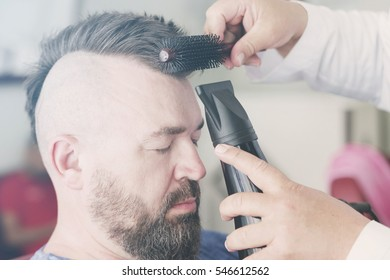 Male barber makes hair styling using a hair dryer of a adult bearded man with a mohawk. Toned