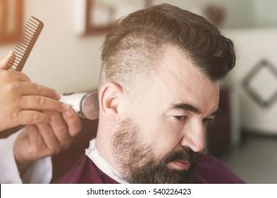 Male barber makes a mohawk hairstyle using clipper at the adult man with beard. Toned