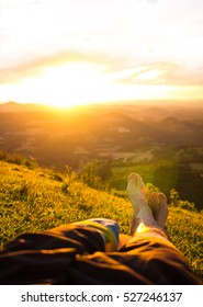 Male bare feet relaxing on green grass on the top of a mountain at sunset, copy space