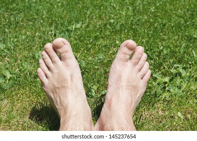 male barefoot on green grass in sunny day