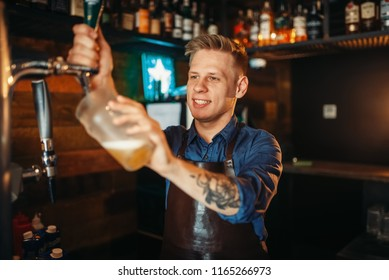 Male barman pouring beer at the bar counter