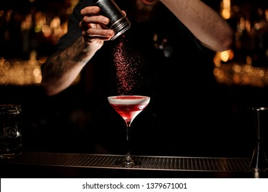 Male bartender decorates red alcohol cocktail in glass on bar counter