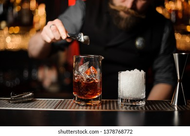 Male bartender in gray shirt adds ice with ice tongs in glass with alcohol cocktail