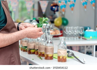 Male bartender hands holding mint herb, preparing summer refreshing lemonade drink for big friendly party. Non-alcoholic cocktail for a group of friends.