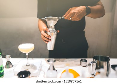 Male bartender make a coconut thaistyle cocktail at modern white stone counter bar.