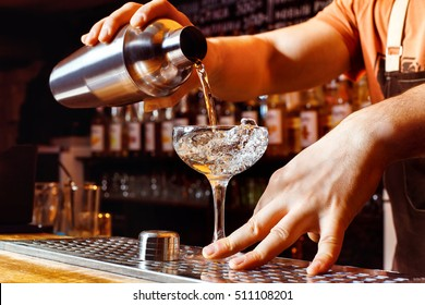 Male bartender is making cocktail pouring alcohol from shaker to glass at bar background. Barman at work.