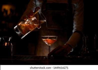 Male bartender pouring a brown alcoholic cocktail from the measuring cup to the glass on the bar counter in the dark blurred background in the dark